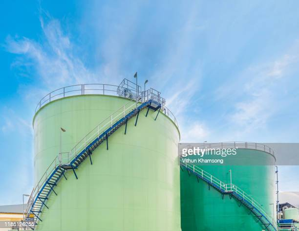 large industrial tanks for petrol and oil with blue sky.fuel tanks at the tank farm. metal stairs on the side of an industrial chemical container.staircase on big fuel tank - tanque de armazenamento imagens e fotografias de stock
