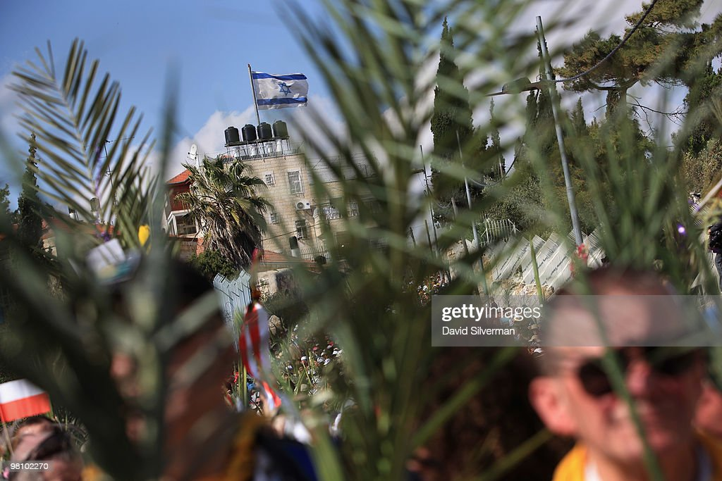 A large Israeli flag flutters in the breeze from a right-wing Jewish settlement behind Christian pilgrims as they walk down the Mount of Olives to the Old City during the traditional Palm Sunday procession on March 28, 2010 in Jerusalem, Israel. Palm Sunday, which marks the start of Holy Week, is a landmark in the Christian calendar, marking the triumphant return of Jesus to Jerusalem the week before his death when a cheering crowd greeted him waving palm leaves.