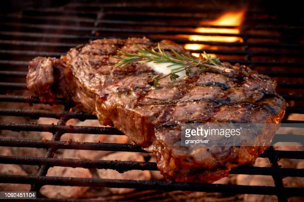 large juicy beef rib eye steak on a hot grill with charcoal and flames - beef stock pictures, royalty-free photos & images