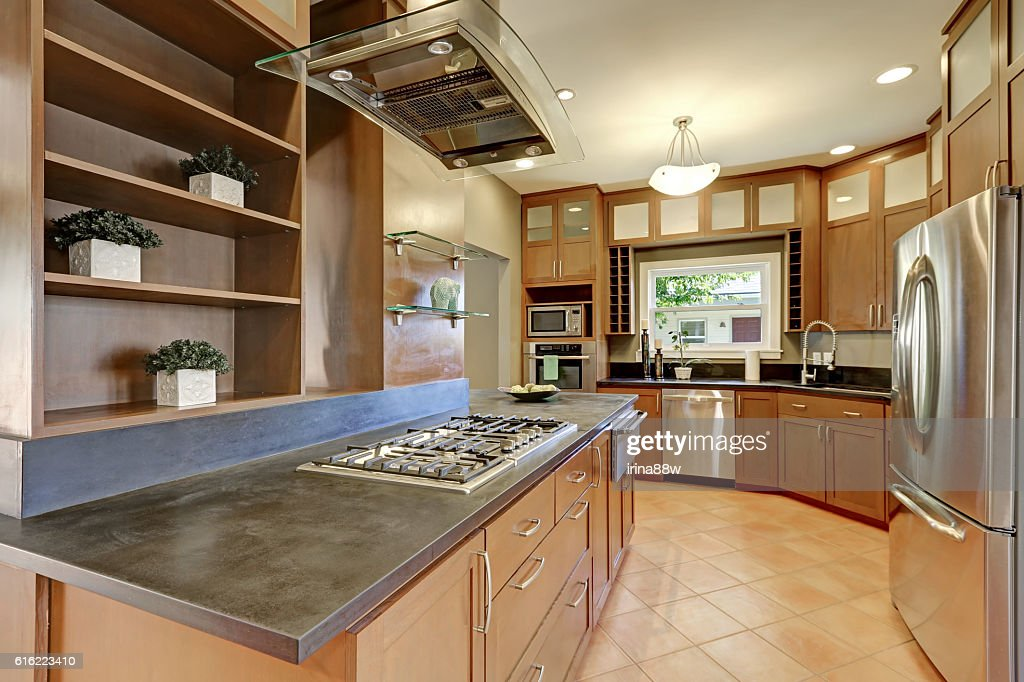 Large kitchen room interior with brown cabinets and steel appliances : Stock-Foto