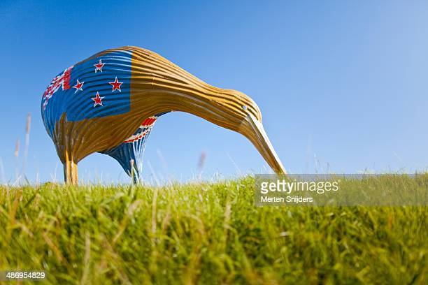 Large Kiwi statue made from metal containing the New Zealand flag on his bum with his beak into the grass field like its eating Caught on Maniapoto...
