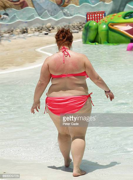 large lady walking in pool wearing bikini - swimwear stock photos and pictures