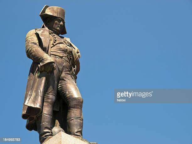 A large lifelike statue of Napoleon in Ajaccio by blue sky.