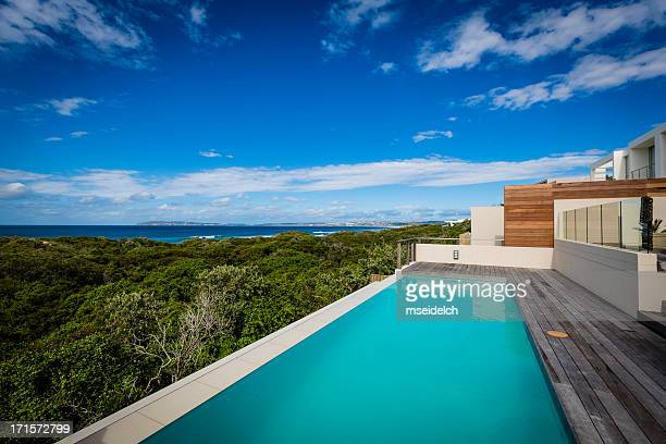 Large luxury villa pool and deck on a cliff with ocean view