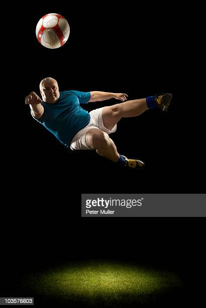 large man doing flying volley - fat soccer players foto e immagini stock