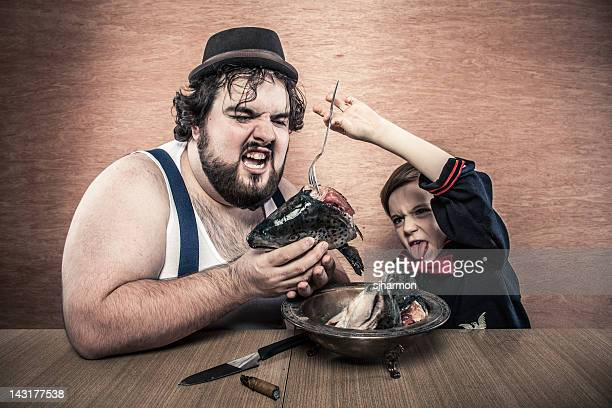 Large Man Enjoys Bowl of Raw Fish Heads with Boy