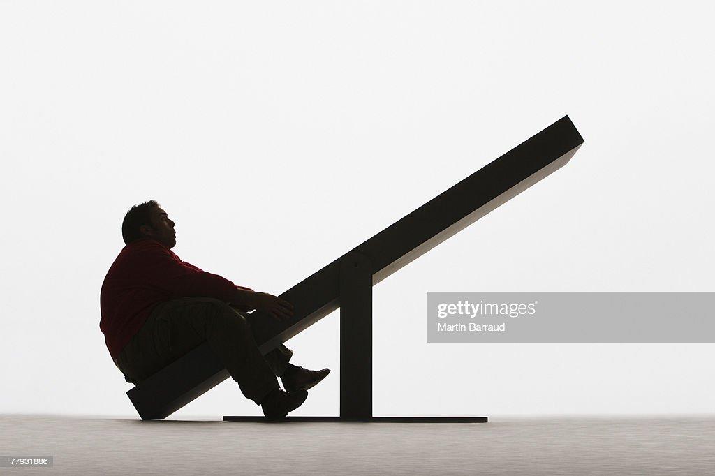 Large man on unbalanced plank : Stock Photo