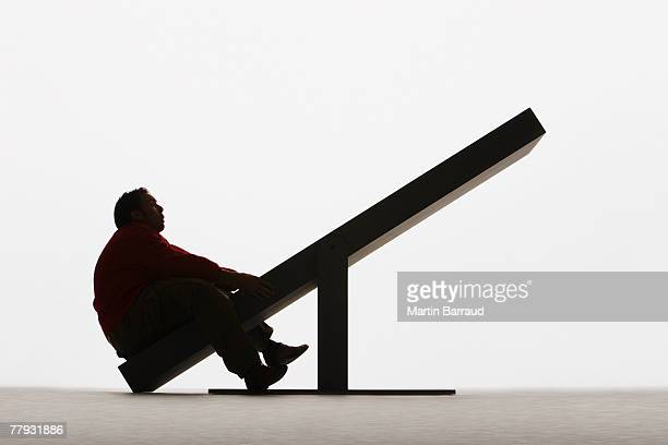 Large man on unbalanced plank