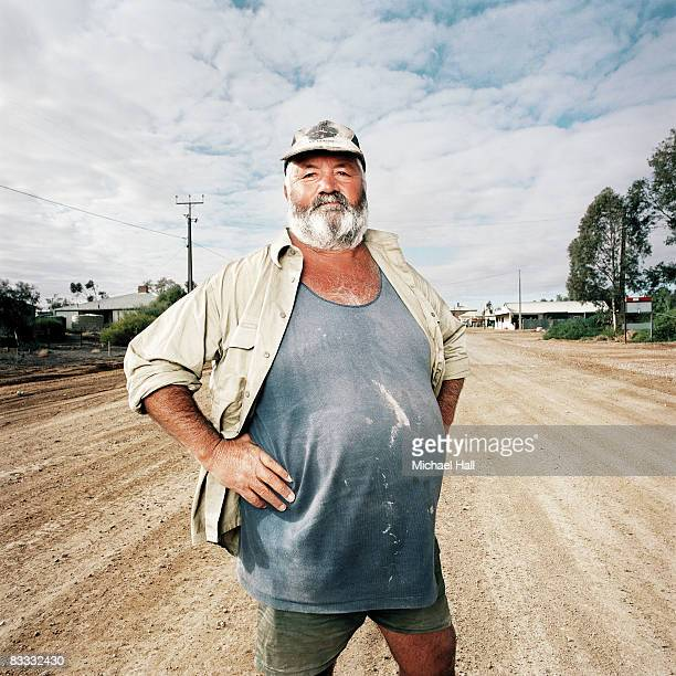 Large man standing on dirt road
