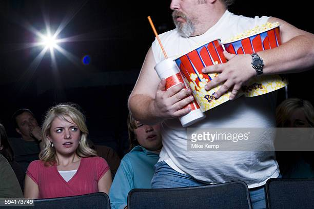 Large man with buckets of popcorn and drink at movie theater