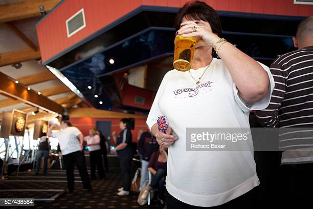 A large manly woman sips a pint of lager during a darts tournament where she competes in an England Open tournament at the Bunn Leisure Holiday Park...