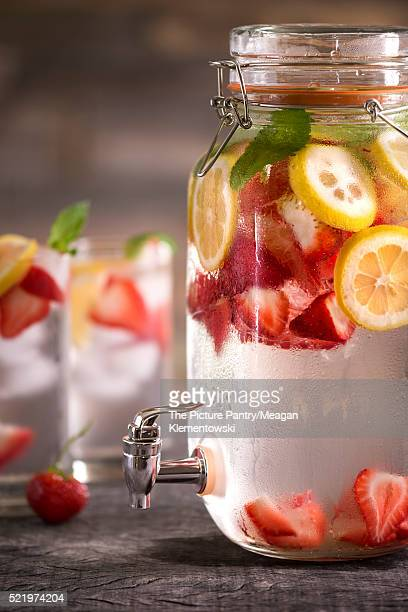 Large mason jar with spout filled with infused water of lemon, s