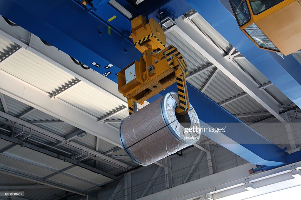 A large mechanical crane with a huge steel coil : Stock Photo