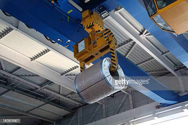 A large mechanical crane with a huge steel coil