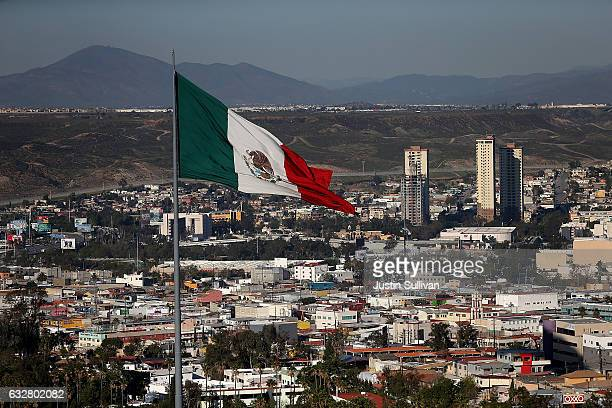 A large Mexican flag flies over the city on January 26 2017 in Tijuana Mexico US President Donald Trump announced a proposal to impose a 20 percent...