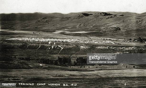 Large military training camp photographed from a distant hill is the subject of this 1912 postcard taken in Vernon, British Columbia, Canada.