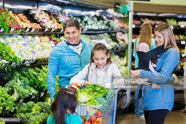 Large mixed race family shopping together for groceries