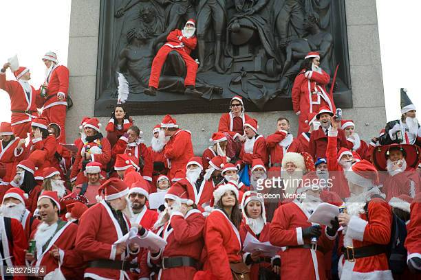 A large mob of bawdy Santas pose for a group photograph and sing their own unique Christmas carols at Nelson's Column in Trafalgar Square during the...