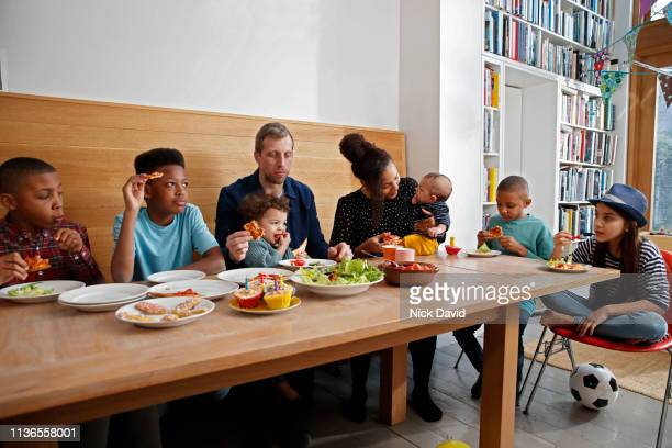 Large multi ethnic family having food at kitchen table