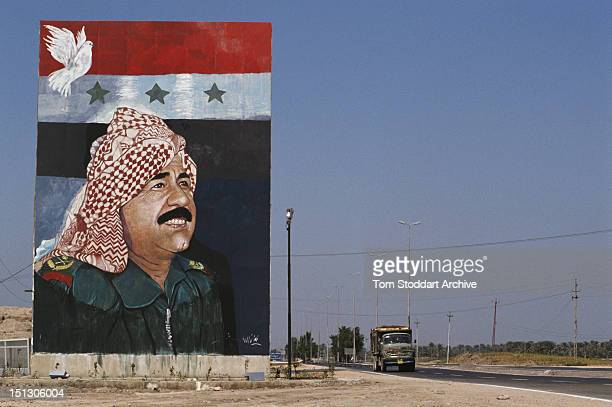 A large mural showing President Saddam Hussein with a dove of peace and the flag of Iraq in a Baghdad street September 1989