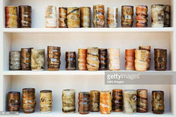 A large number of ceramic jars arranged in rows on shelves. Different firing and glazing techniques, and a variety of natural colours.