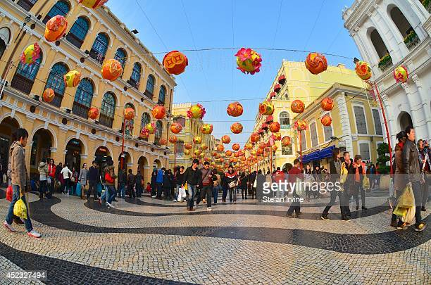 A large number of colourful lanterns in preparation for Chinese New Year hanging above the crowds at the historical Largo do Senado or Senate Square...