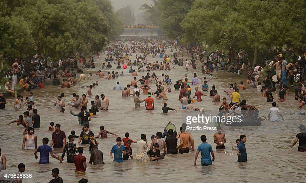 A large number of Pakistani people enjoy swimming in a canal to get some relief from the scorching hot weather during the summer season in Lahore