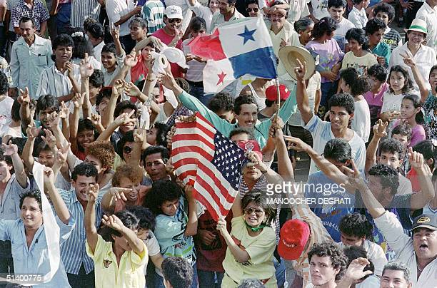 Large number of Panamanians opposed to General Manuel Antonio Noriega wave American and Panamanians flags outside a military post 22 December 1989....