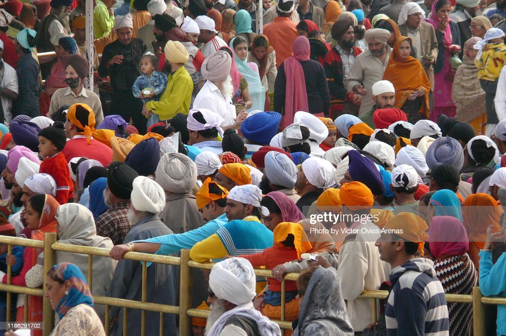 Large number of Pilgrims waiting to enter the Harmandir Sahib (The Golden Temple) and the clock tower in Amritsar, Punjab, India : Stock Photo