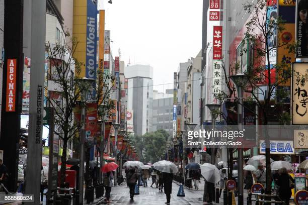 A large number of signs in Japanese are visible on a shopping street where people walk and holds umbrellas on a rainy day in the Ikebukuro district...