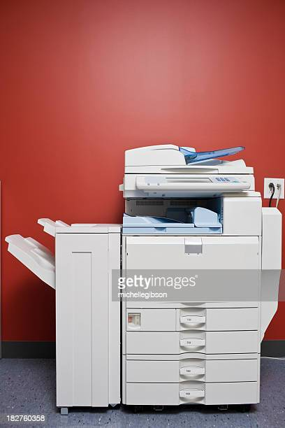 Large office photocopier in front of red wall