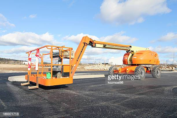 Large, orange boom lift under a cloudy sky