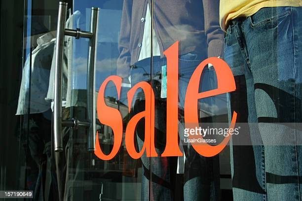 Large orange sale sign on a clothes shop