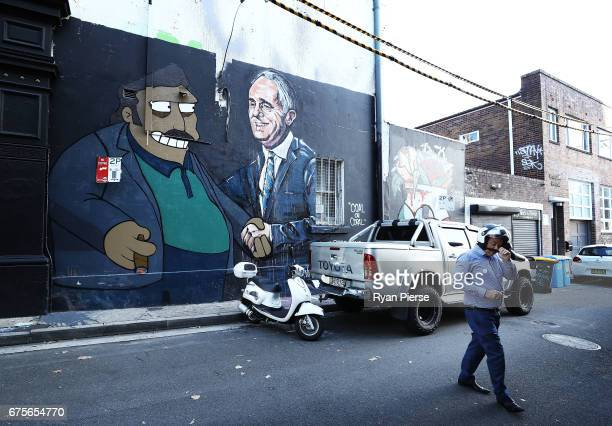 A large painted mural on the side of a building in Chippendale depicts Prime Minister Malcolm Turnbull shaking hands with The Simpsons character Fat...