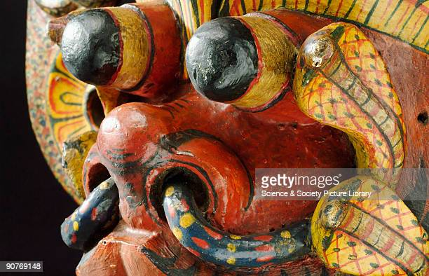 Large painted wooden polychrome mask representing a redfaced demon with cobra canopied headdress and cobras on lotus disc ear pieces associated with...