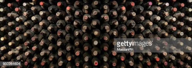 Large pannel for decorating a restaurant room whit old wine bottles stored in a cellar for aging