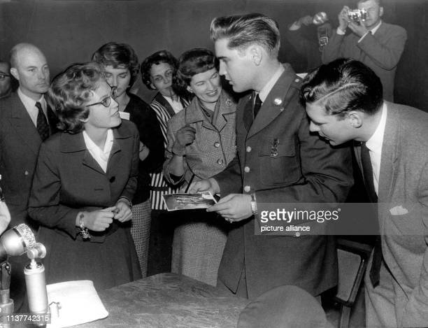 Large part of the journalists lunge at the prominent US soldier Elvis Presley to ask for an autograph, as soon as the press conference in Friedberg...