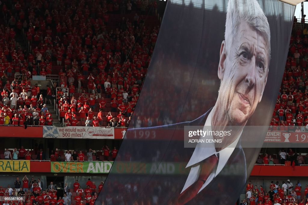 TOPSHOT - A large photograph of Arsenal's French manager Arsene Wenger is suspended from the roof as players take a lap of honour on the pitch after the English Premier League football match between Arsenal and Burnley at the Emirates Stadium in London on May 6, 2018. - Arsene Wenger bids farewell to a stadium he helped to build in more ways than one when he leads Arsenal at the Emirates for the final time at home to Burnley on Sunday. Wenger's final season after 22 years in charge is destined to end in disappointment after Thursday's Europa League semi-final exit. (Photo by Adrian DENNIS / AFP) / RESTRICTED TO EDITORIAL USE. No use with unauthorized audio, video, data, fixture lists, club/league logos or 'live' services. Online in-match use limited to 75 images, no video emulation. No use in betting, games or single club/league/player publications. /