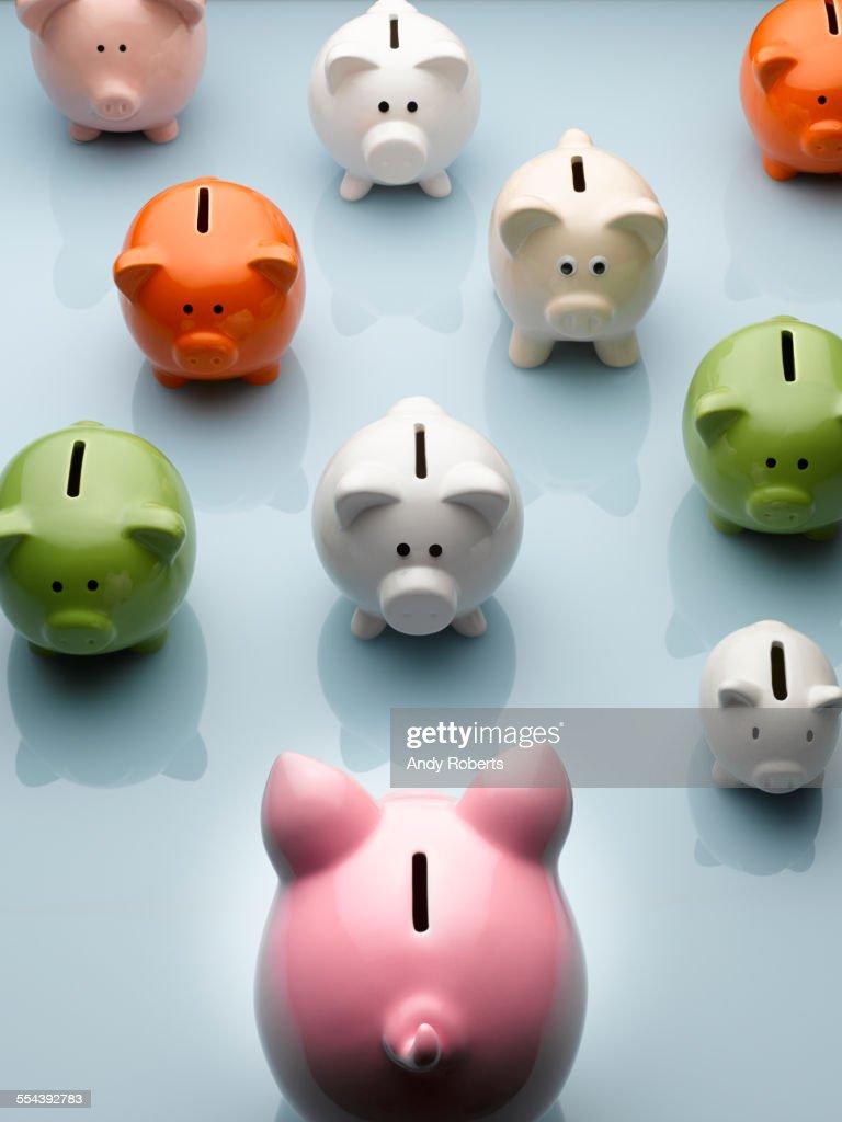 Large piggy bank facing smaller multicolor piggy banks still life : Foto de stock