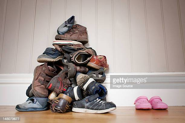 Large pile of boy's shoes beside one pair of girl's shoes