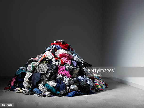 Large pile of clothes in an empty room.