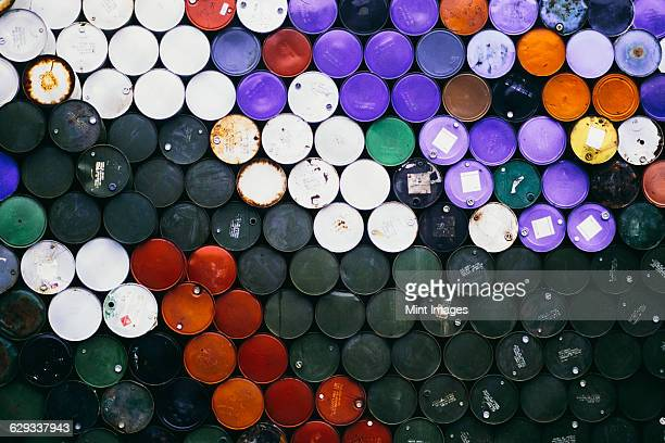 large pile of colourful petroleum barrels stacked up in colour co-ordinated way. - oil barrel stock pictures, royalty-free photos & images
