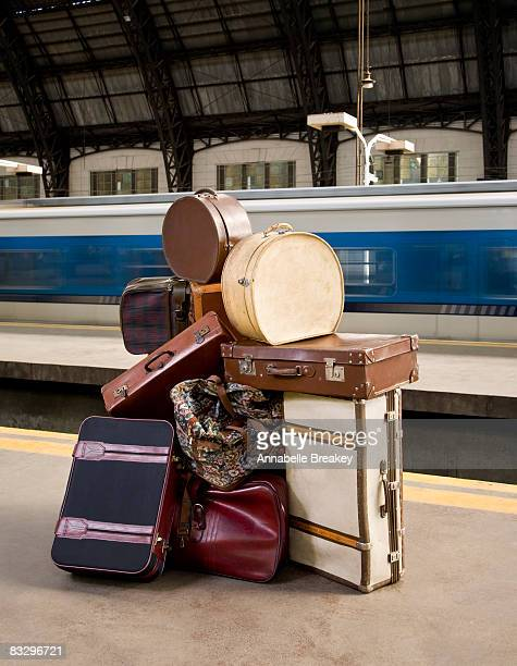 Large pile of luggage on train platform.