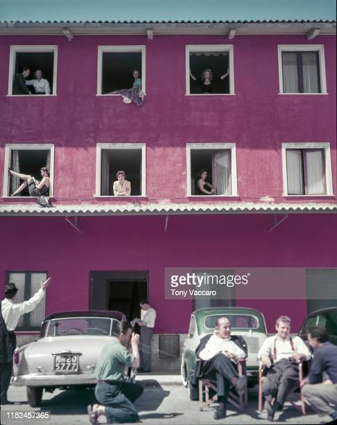 large pink building with two stories high and 8 windows where some extras are sitting on the ground floor a car is parked and man is waiving at the...