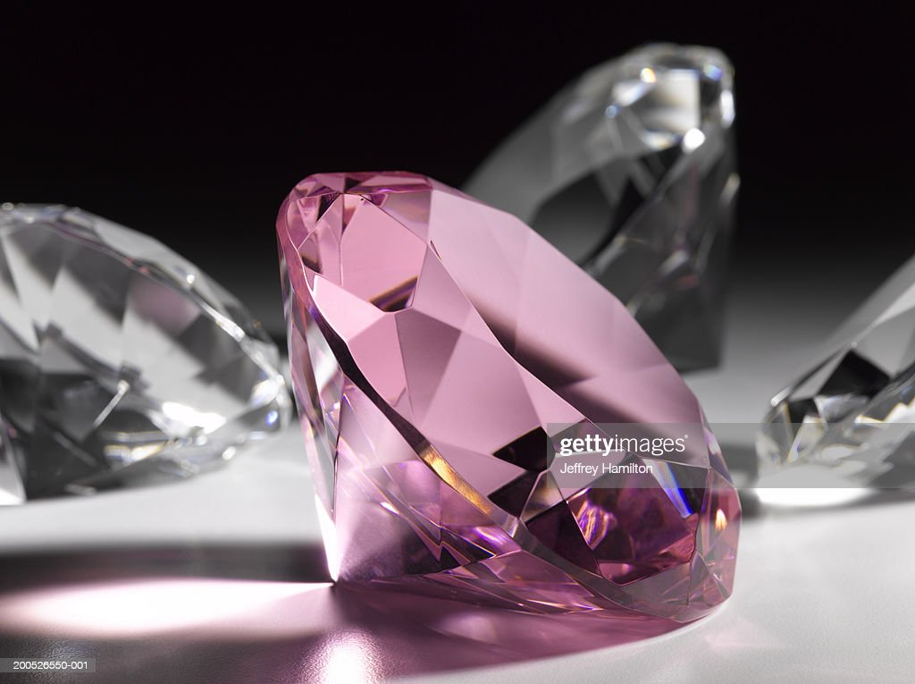 Large pink diamond surrounded by clear diamonds, close-up (still life) : Stock Photo
