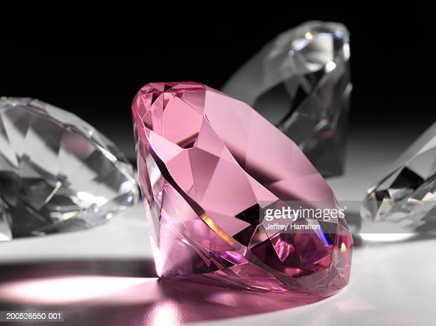 large pink diamond surrounded by clear diamonds, close-up (still life) - diamond gemstone stock pictures, royalty-free photos & images