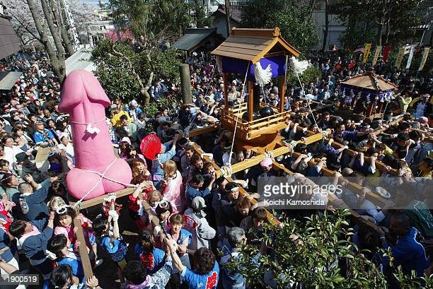 Large pink penis is carried through the participating crowds April 6, 2003 in Kawasaki, Japan. People of all ages participate in the annual Penis...