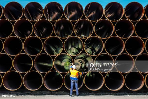 Large pipes for the Baltic Sea pipeline Nord Stream 2 on a storage area in the ferry port of Sassnitz/Neu Mukran An employee of the responsible...