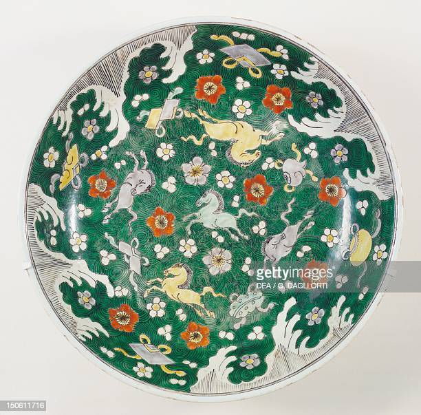 Large plate decorated with horses galloping among red flowers and Buddhist symbols porcelain China Chinese Civilisation Qing dynasty beginning of...