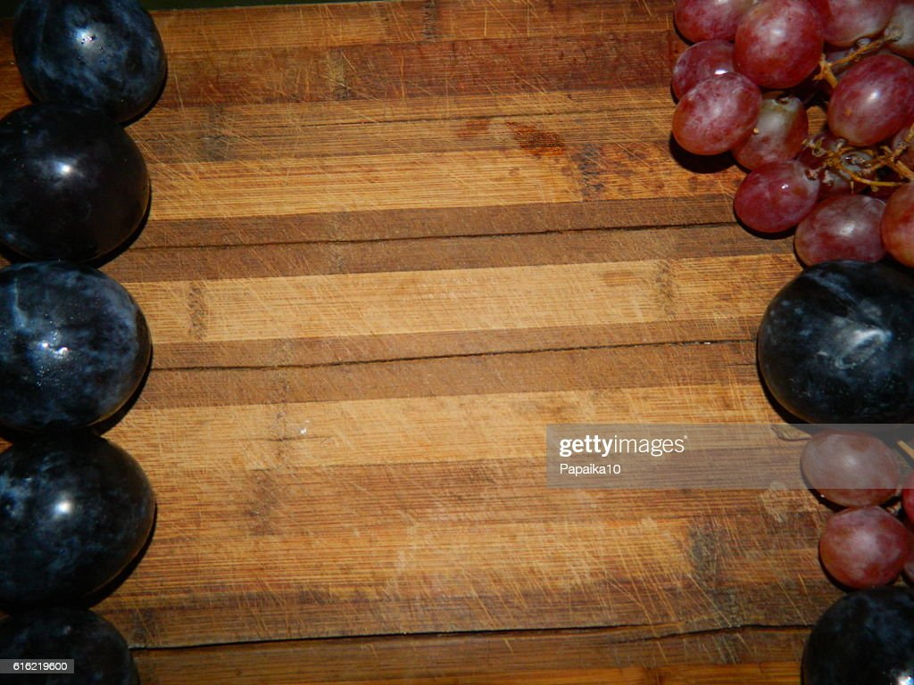 Large  plums and grapes on the sides of the wooden board : Stock-Foto